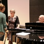 Jeremy Fisher at the piano with Gillyanne Kayes talking to a student